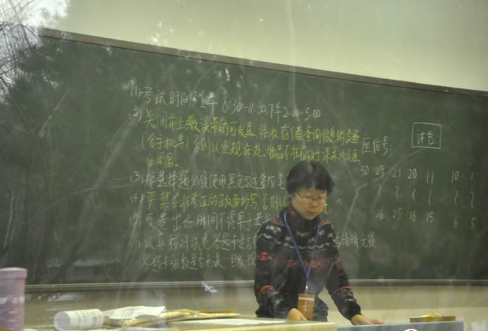 黑板上考试规则,考场监考老师准备考前工作.